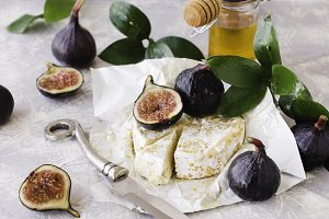 blu cheese, figs and honey on a white marble table, selective focus