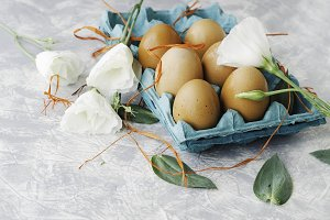 raw eggs in a carton for eggs with white flowers on a marble white table, ready for painting Easter, selective focus