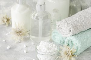 Spa set on a white marble table with a stack of towels, selective focus