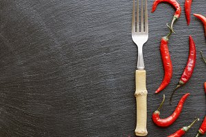 Red chili peppers on a black table with a fork, concept, top view