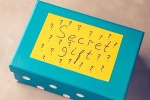 Blue box with paper card written Secret gift