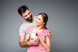 Happy couple holding cup