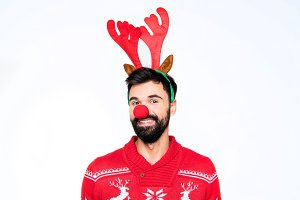 Smiling man in antlers and red nose