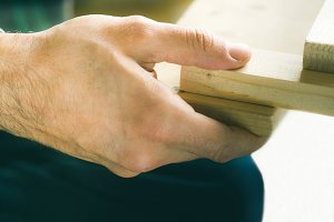 Man crafting wooden object with hands. Lifestyle process