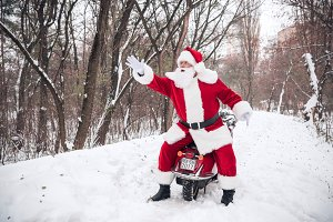 Santa Claus on scooter pointing