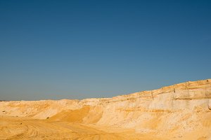 cliff of the yellow orange brown sand soil clay under the bright sunny day with deep blue sky