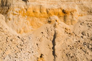 cliff of the yellow orange brown sand soil clay under the bright sunny day. Texture background