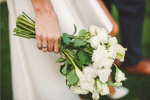 wedding bouquet of gorgeous white roses at bride's hand