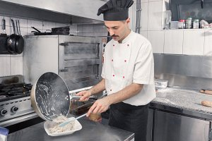chef finishing pasta dish pan plate