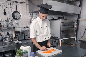 chef cutting carrots board kitchen