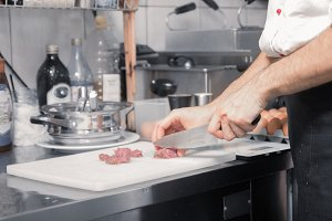 chef closeup knife cutting raw meat