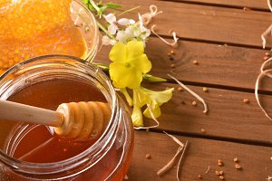 Open jar honey with dipper elevated