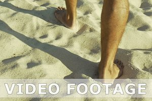 Male feet walking on sand