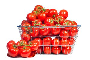 There is a shopping basket full of red ripe tomatoe. Conceptual image of buying vegetables and healthy eating.