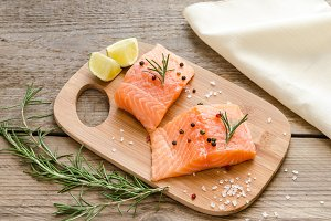 Raw salmon steaks on wooden board