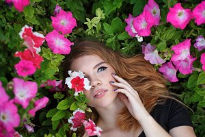 Girl lies in wild flowers.