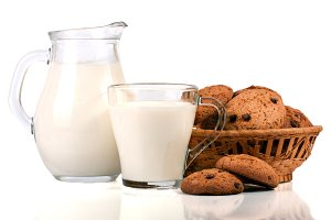 jug and glass of milk with oatmeal cookies in a wicker basket isolated on white background