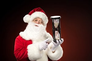 Santa Claus pointing at hourglass