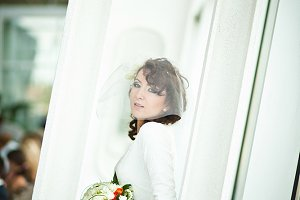 Stylish bride poses in the window