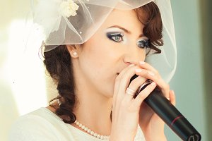 Thoughtful bride holds a microphone
