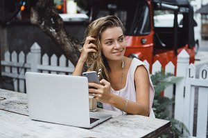 Girl using smartphone and laptop