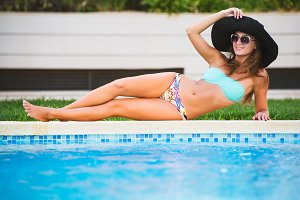 Beautiful tanned sexy girl in bikini and black hat posing at a swimming pool