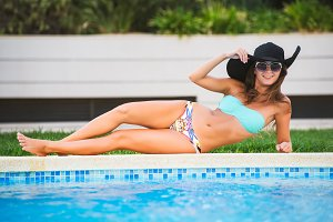 Beautiful tanned sexy girl in bikini and black hat lying at a swimming pool