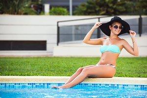 Beautiful tanned sexy girl in bikini and black hat sunbathing at a swimming pool
