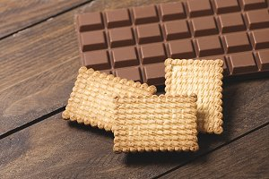 Cookies and chocolate tablet on wooden background. Horizontal shoot.