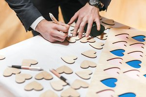 Men writing something on small wooden hearts