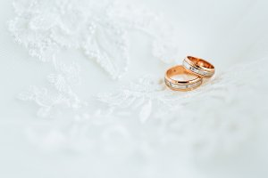 Golden wedding rings on veil. Close-up