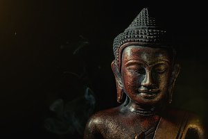 Wooden buddha on black background