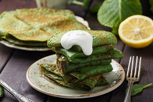 pancakes with spinach and sour cream on wood table