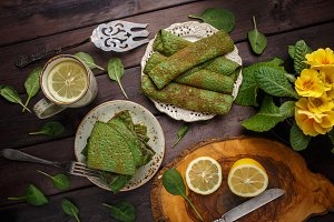 pancakes with spinach on wood table. Top view. Lay flat