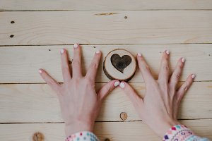 Women's hands hold a wooden heart