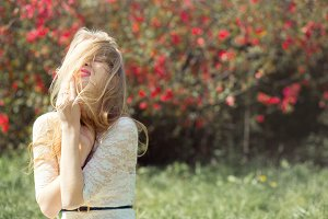 Blonde Young Woman in Spring Garden. Girl with Flying Hair lovely Smiling and Enjoying Blossoming Nature