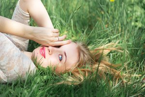 Cute Blue-eyed Blonde Lying on the Spring Grass. Happy young Woman with Red Lips and Natural Make Up in White Lacy Dress Having Fun in Spring Garden