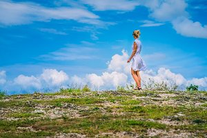 A girl standing on Hill and looking at the white clouds, Teletubbies Hills, Nusa Penida, Bali, Indonesia