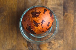 Easter egg in glass on wooden background. Painted brown with spots and cracks. Closeup macro top shot