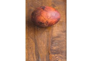 Easter egg on wooden background. Painted brown with spots and cracks. Closeup macro shot with copyspace