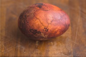 Easter egg on wooden background. Painted brown with spots and cracks. Closeup macro shot
