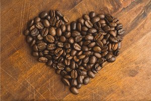 Brown coffee beans in shape of heart, closeup of macro coffee beans for background and texture. On brown wooden board.