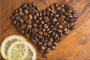 Brown coffee beans in shape of heart with lemon, closeup of macro coffee beans for background and texture. On brown wooden board