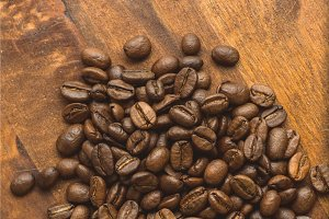 Brown coffee beans in circle shape, closeup of macro coffee beans for background and texture. On brown wooden board.
