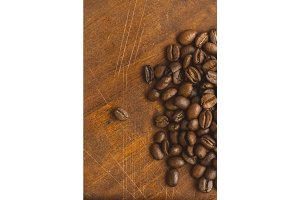 Brown coffee beans in circle shape, closeup of macro coffee beans for background and texture. On brown wooden board. with copy space for your text