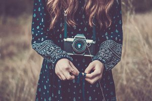 Girl in dress with retro camera