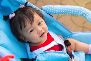 Baby girl smile sitting in stroller
