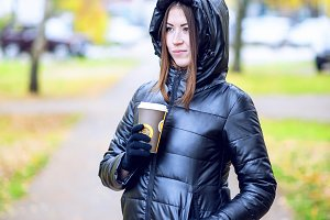 Girl in autumn or spring in a black jacket with a coffee or tea in hand, outdoor. Resting in the city. Life style. Business woman in the hood.