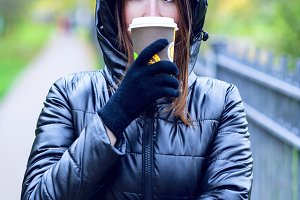 Girl in autumn or spring in a black jacket. He drinks coffee or tea in hand outdoors. Resting in city. Life style. Business woman in the hood.