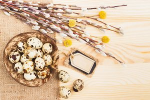 Quail eggs in the bowl and bouquet of dry flowers, wooden background, top view